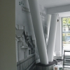 Oklejenie ściany biura nieruchomości INVESTDOM foto-tapetą produktową wydrukowana w skali szarości.
