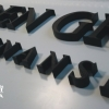Litery przestrzenne malowane na czarną satynę na panelu z dibondu. Logowanie biura. Advert Studio