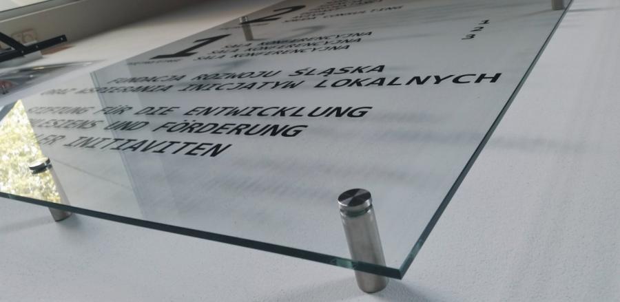 szklany panel z liternictwem z grafiki plotowanej z folii czarnej, tablica montowana na dystansach przez Opolska firme